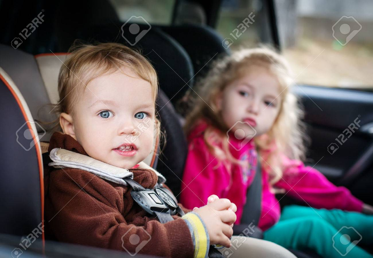 cute small children in car seats in the car stock photo - Small Children Images