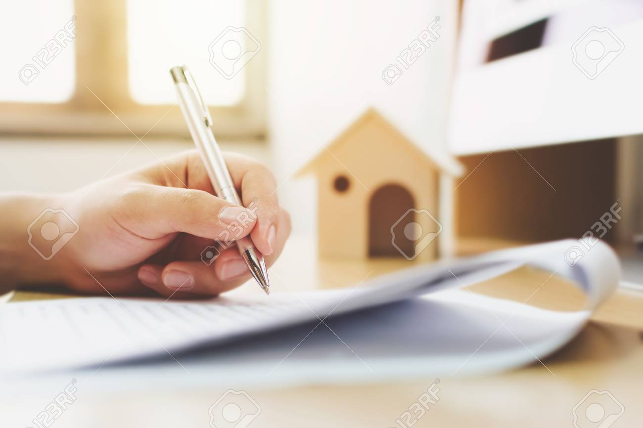 Close up hand of man signing signature loan document to home ownership. Mortgage and real estate property investment - 105210874