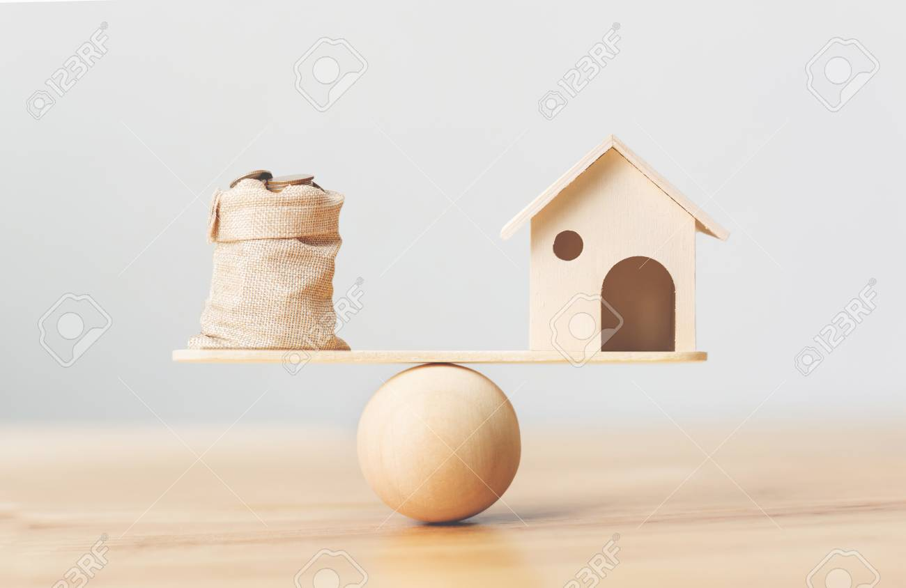 Wooden home and coins money in bag on wood scales. Property investment and house mortgage financial real estate concept - 105928249