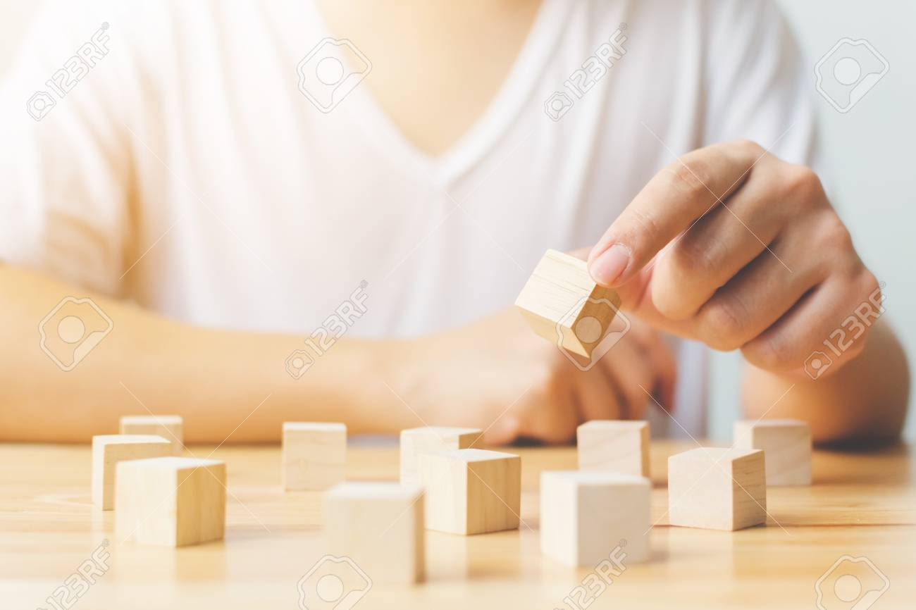 Brain therapy rehabilitation cognitive psychological testing. Hand holding wood block cube therapy equipment - 114809185