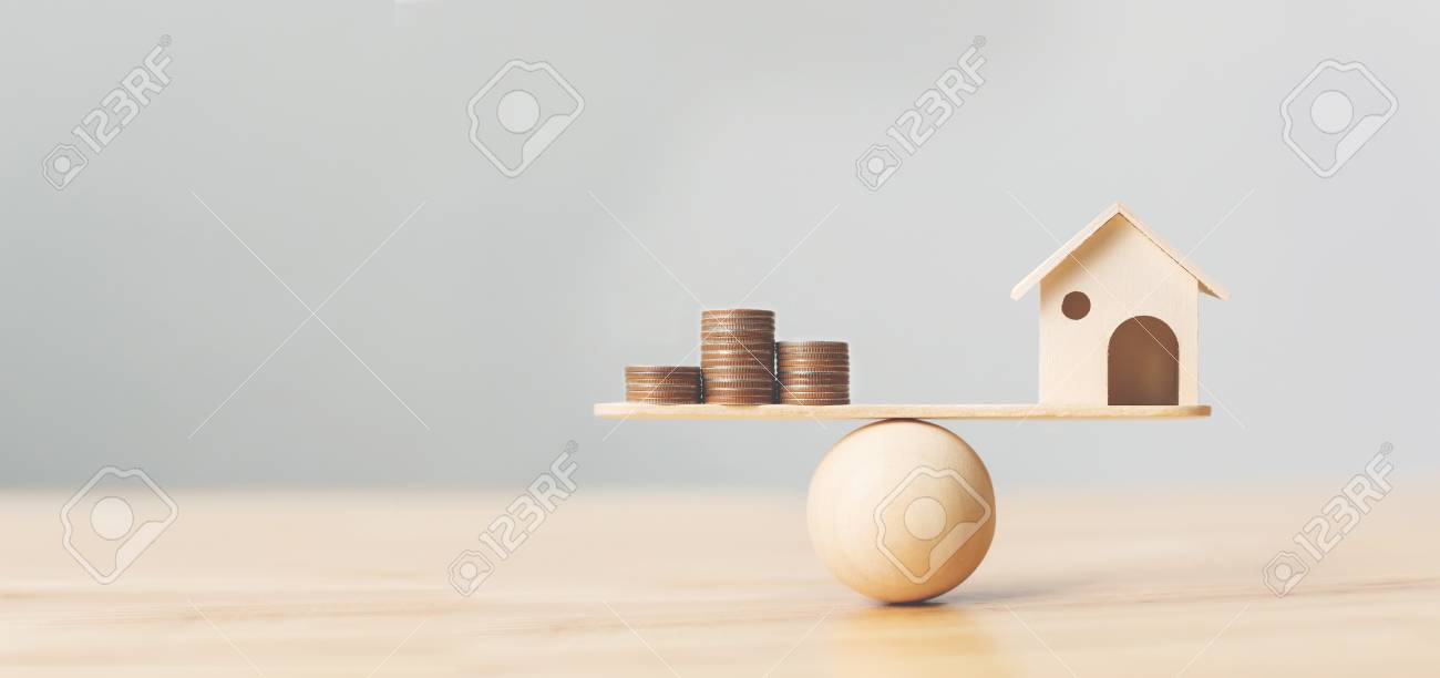 Wooden home and money coins stack on wood scale. Property investment and house mortgage financial real estate concept - 126131349