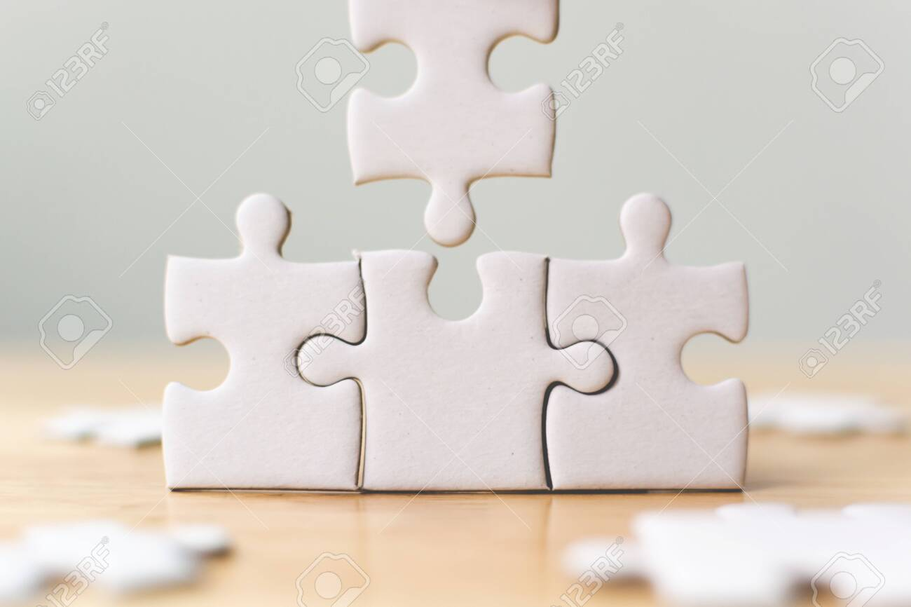 White jigsaw puzzle connecting together. Team business success partnership or teamwork concept - 142149048