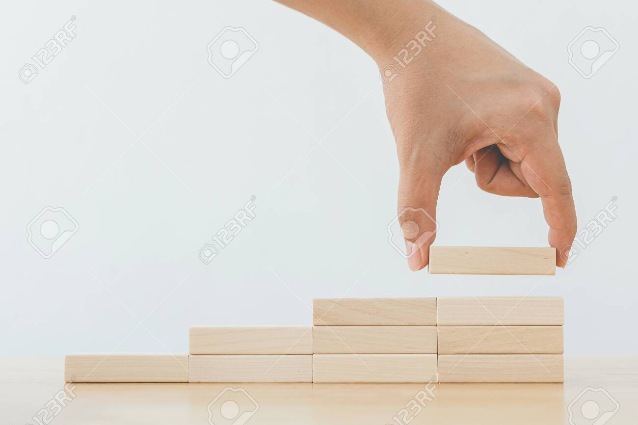 Hand arranging wood block stacking as step stair. Ladder career path concept for business growth success process - 146657846