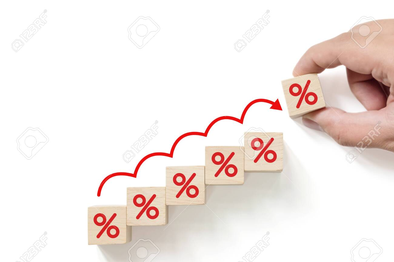 Interest rate financial and mortgage rates concept. Hand putting wood cube block increasing with icon percentage symbol upward direction - 147315451