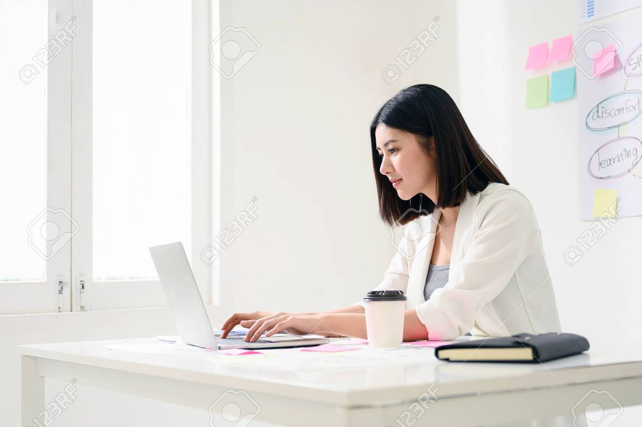 Concept of work from home. Young asian business woman working on computer laptop in office room with paperwork document on desk - 150062161