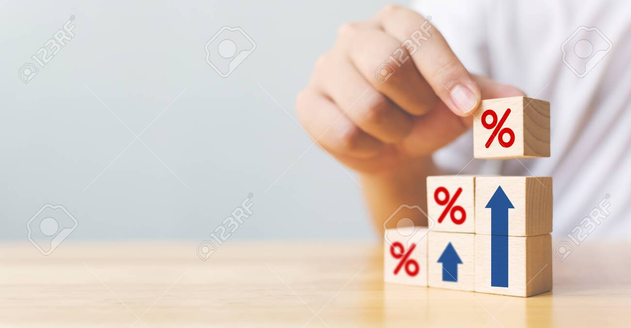 Hand arranging wood block stacking as step stair with sign percent and arrow up symbol. Interest rate financial and mortgage rates concept - 154554010