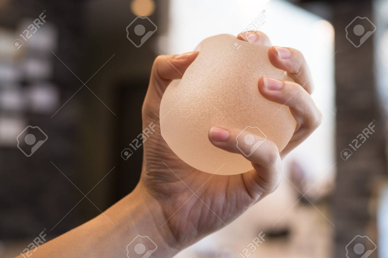 1a122d8667 Silicone breast implant on hands Stock Photo - 102930146