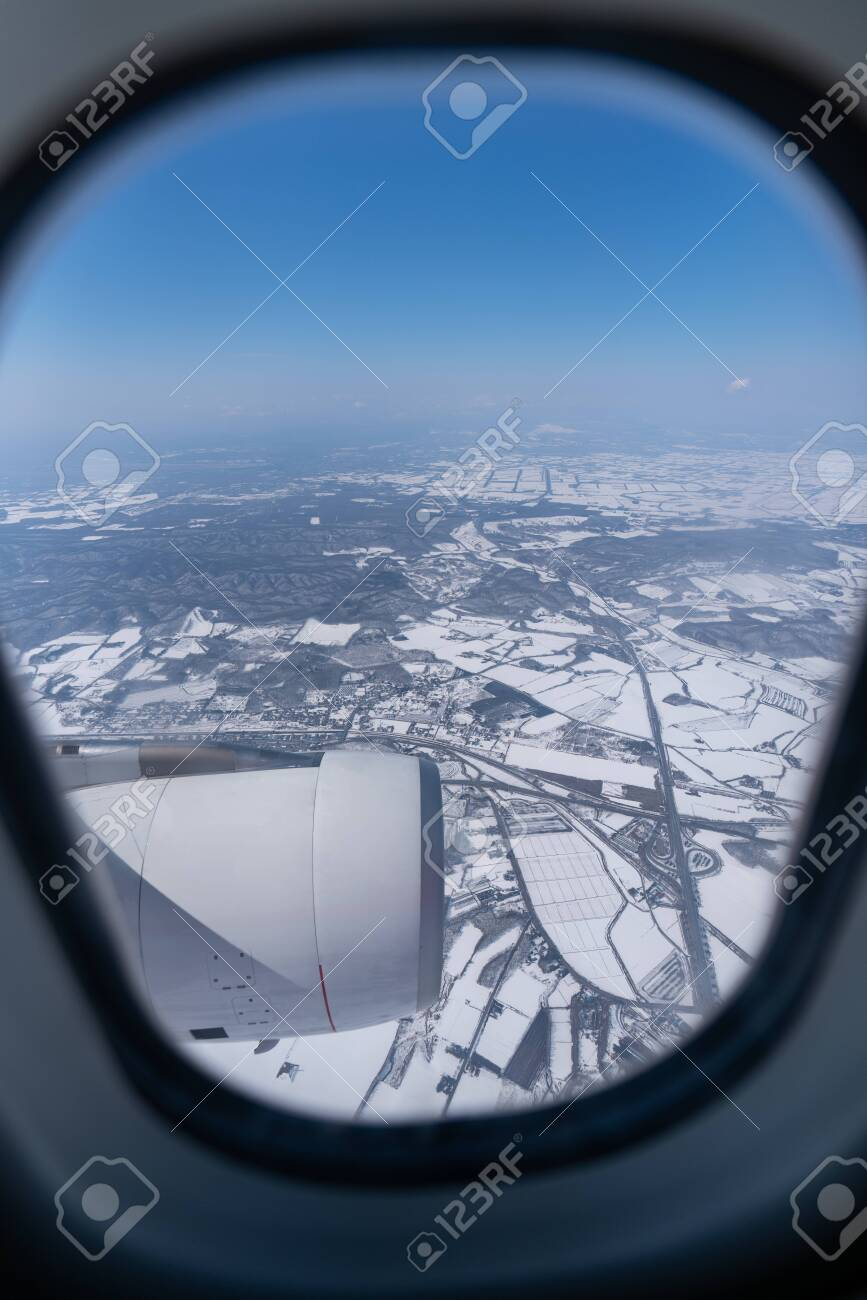 View Of Beautiful City Covered By Snow From A Airplane Window