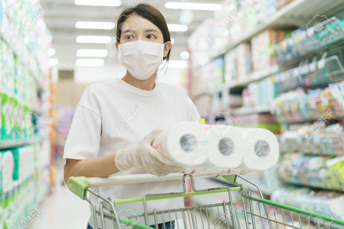 Woman wearing surgical mask and gloves, buying toilet paper roll in supermarket. Panic shopping after coronavirus pandemic. - 145051663