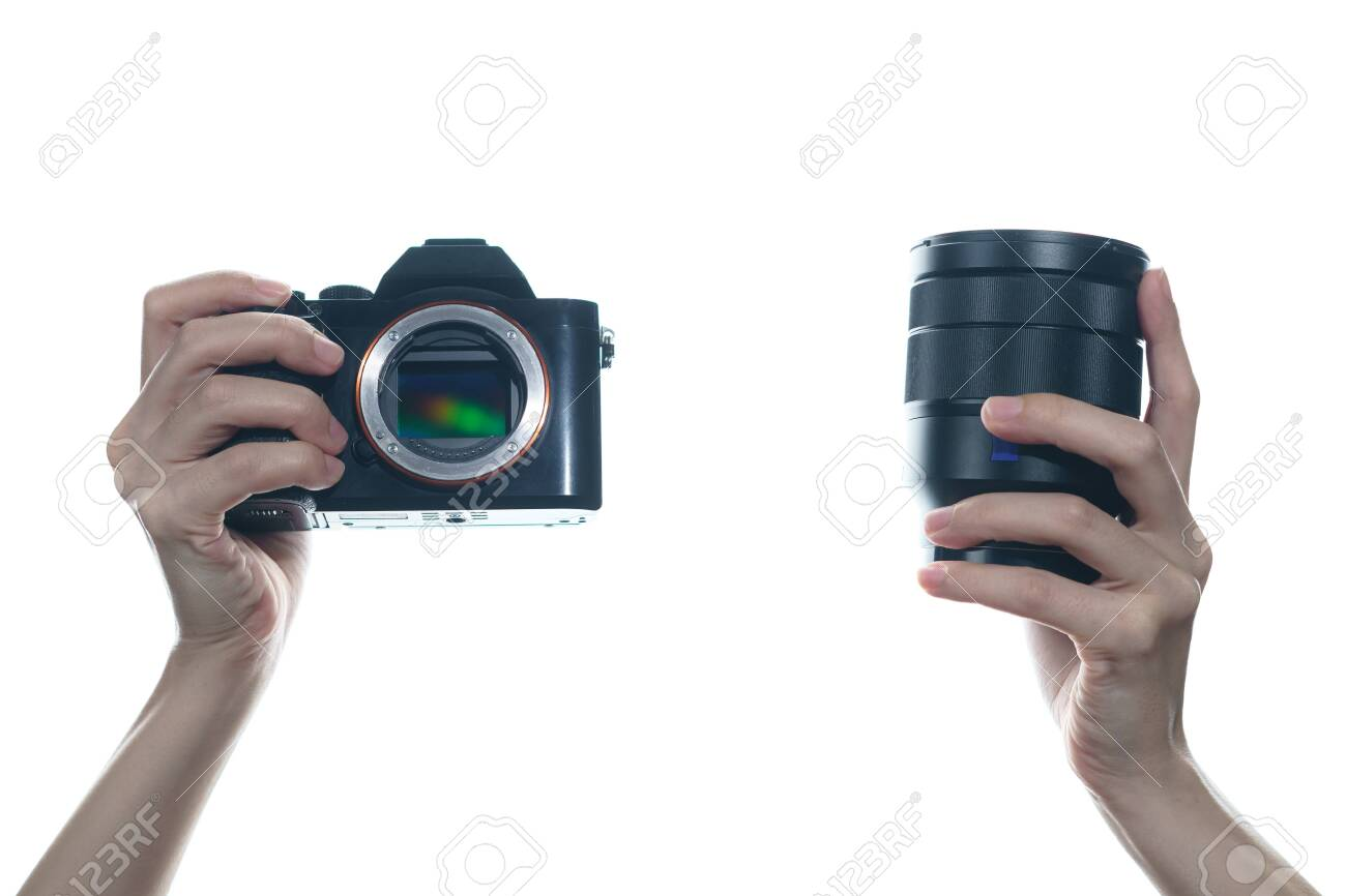 Woman hand holding camera and lens on white background. - 148350260