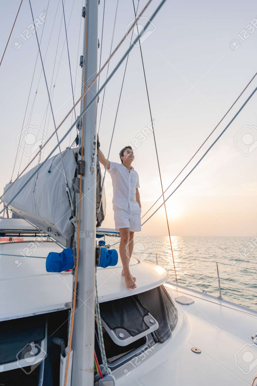 Man in white shirt standing on yacht looking at beautiful sunset. - 168808115