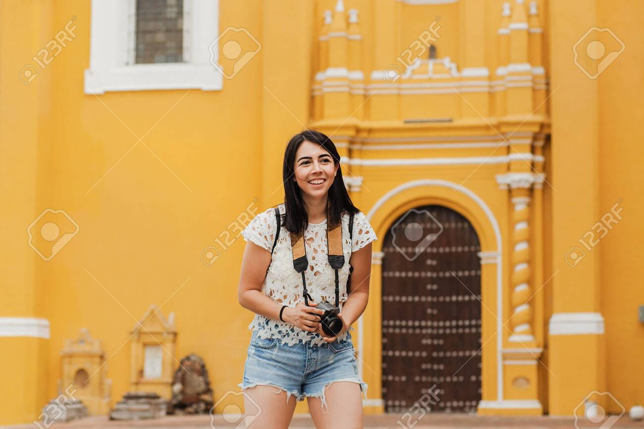 Traveling Latin Woman tourist backpackers holding a camera photo in Mexico city - 140781185