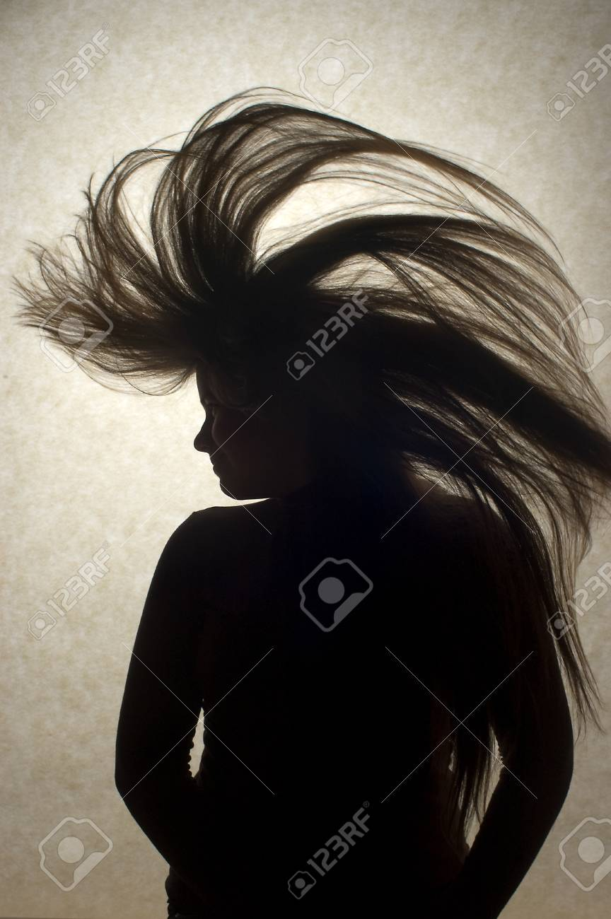A silhouette of a young woman flipping her long hair Stock Photo - 40481667