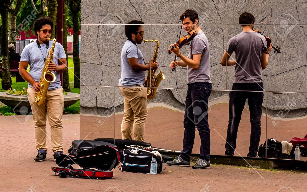 street performer in amsterdam with reflection wall, playing violin and saxophon music - 140730769