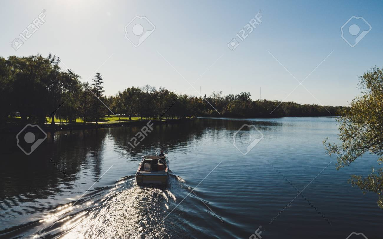 boat from behind driving on a beautiful river in a park during sunny summer day on toronto island lak ontario - 108906179
