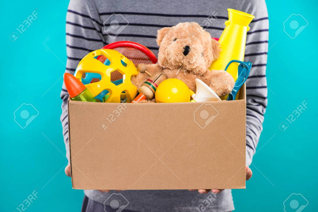 Male volunteer holding donation box with old toys. - 81072428