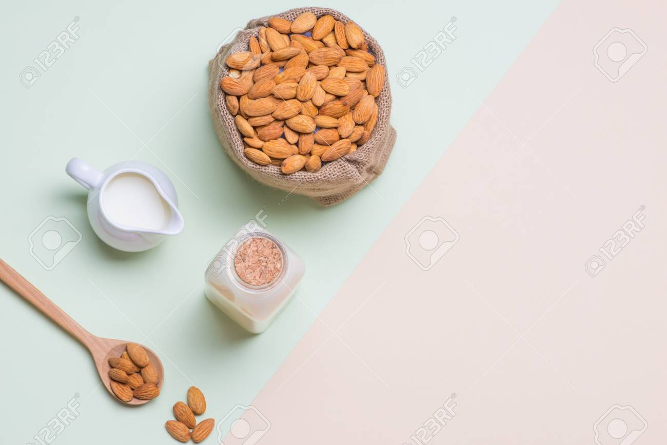Almonds and milk bottle on light background. Almond nuts in spoon. - 82344873