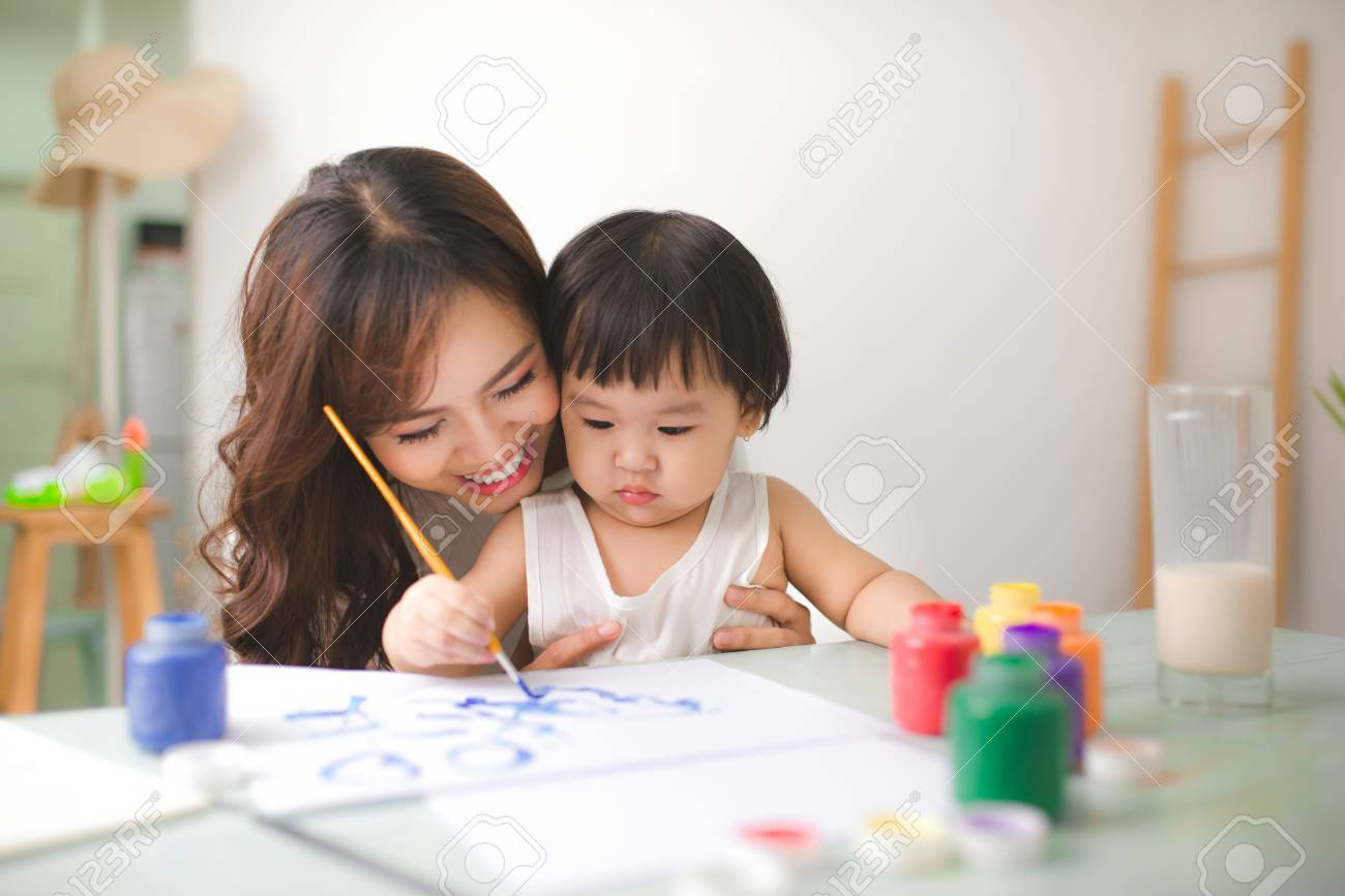 Happy family mother and daughter together paint. Asian woman helps her child girl. - 83236318