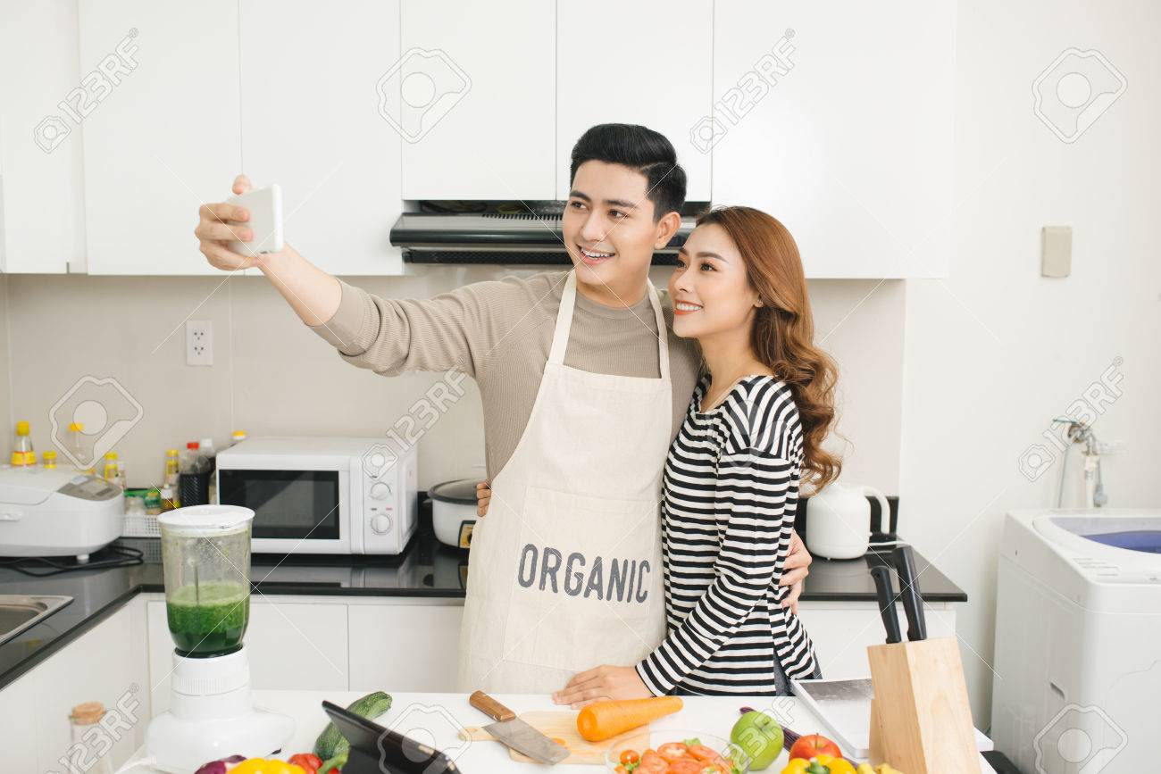 Happy Asian Couple Smiling And Cooking In The Kitchen Doing Selfie ...