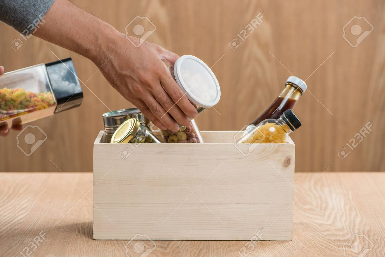 Volunteer with donation box with food stuffs on wooden background - 84984477