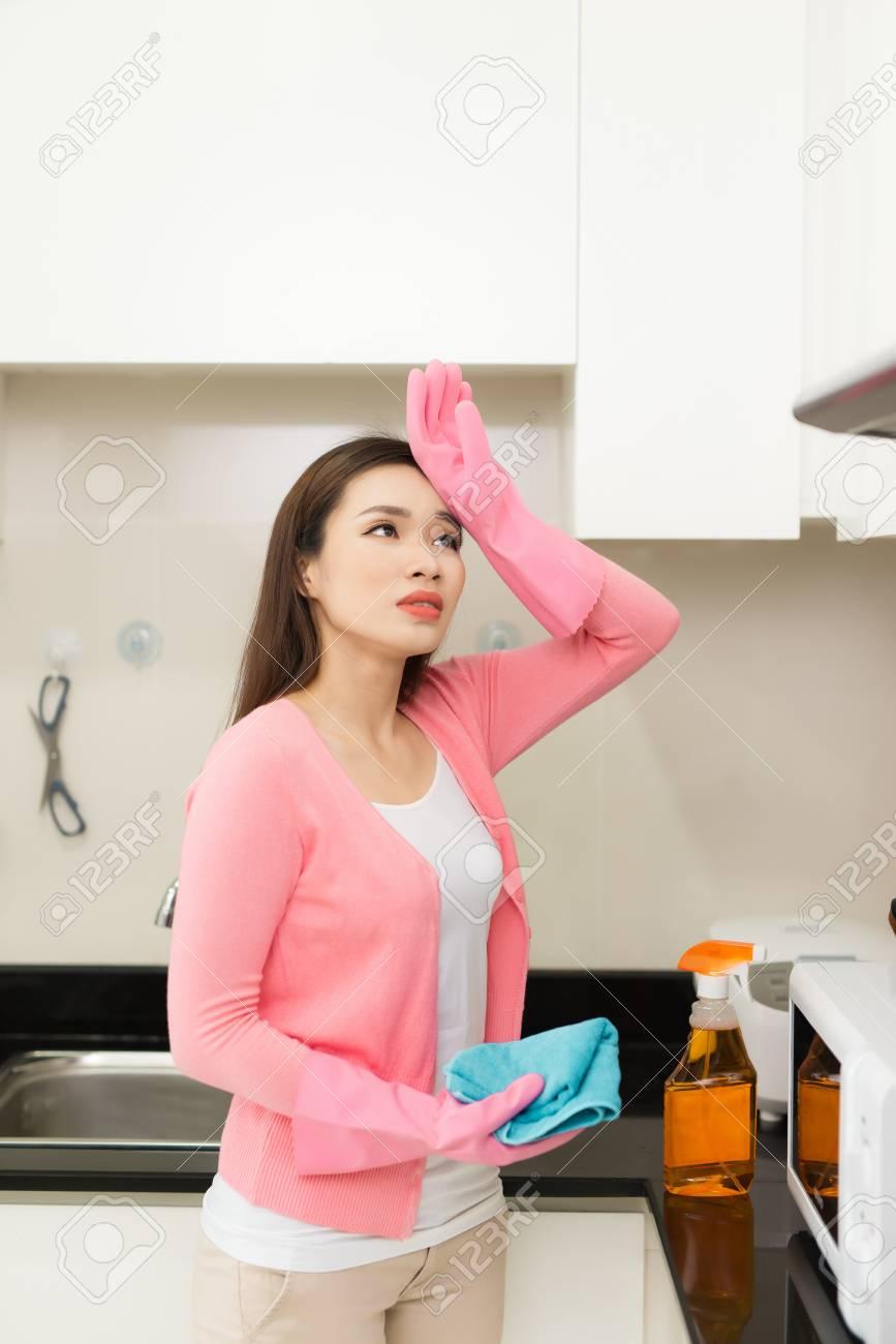 Nettoyer Les Placards De Cuisine jeune femme en gants de caoutchouc rose, nettoyage d'une surface de placard  de cuisine blanc