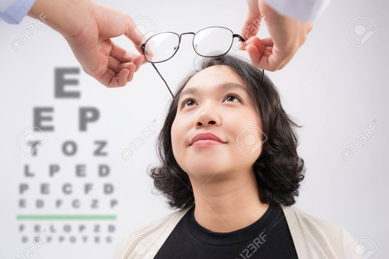 c03744557be6 New glasses. Optometrist giving asian woman eyeglasses to try Stock Photo -  87861809