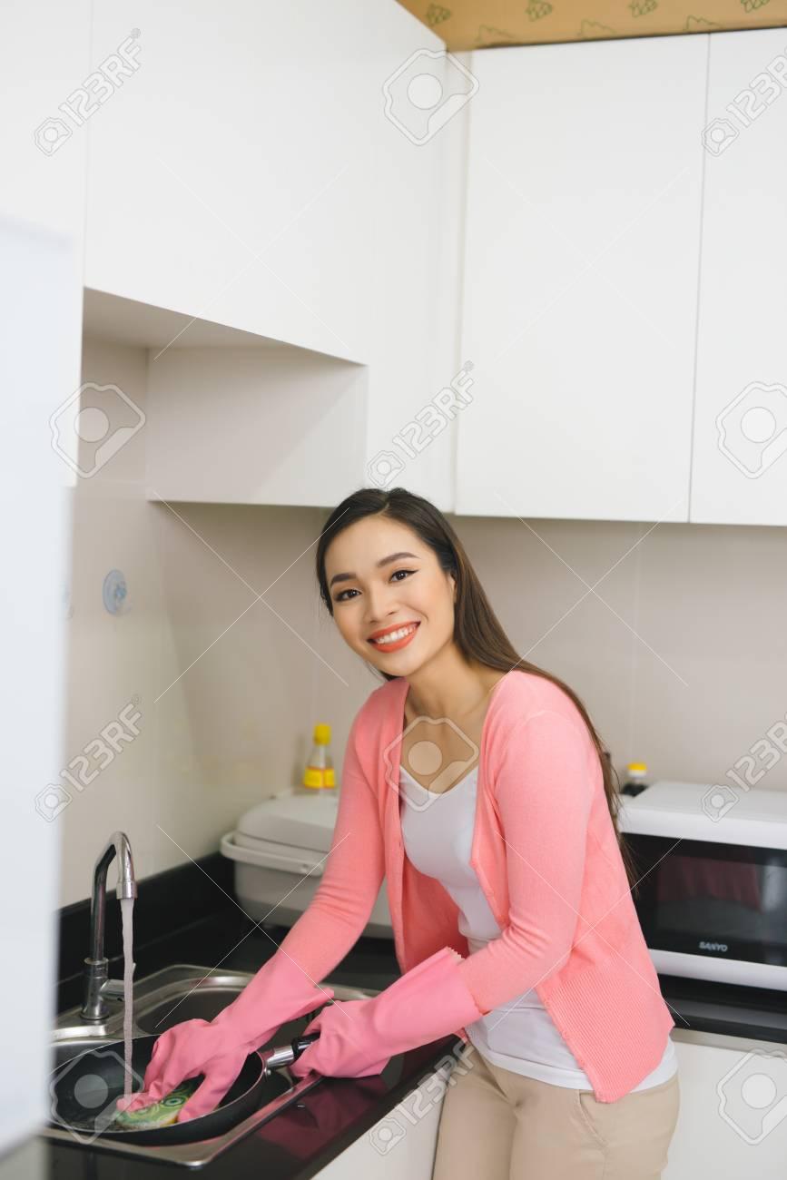 Nettoyer Les Placards De Cuisine portrait de jeune femme séduisante nettoyer une surface de placard de  cuisine blanche