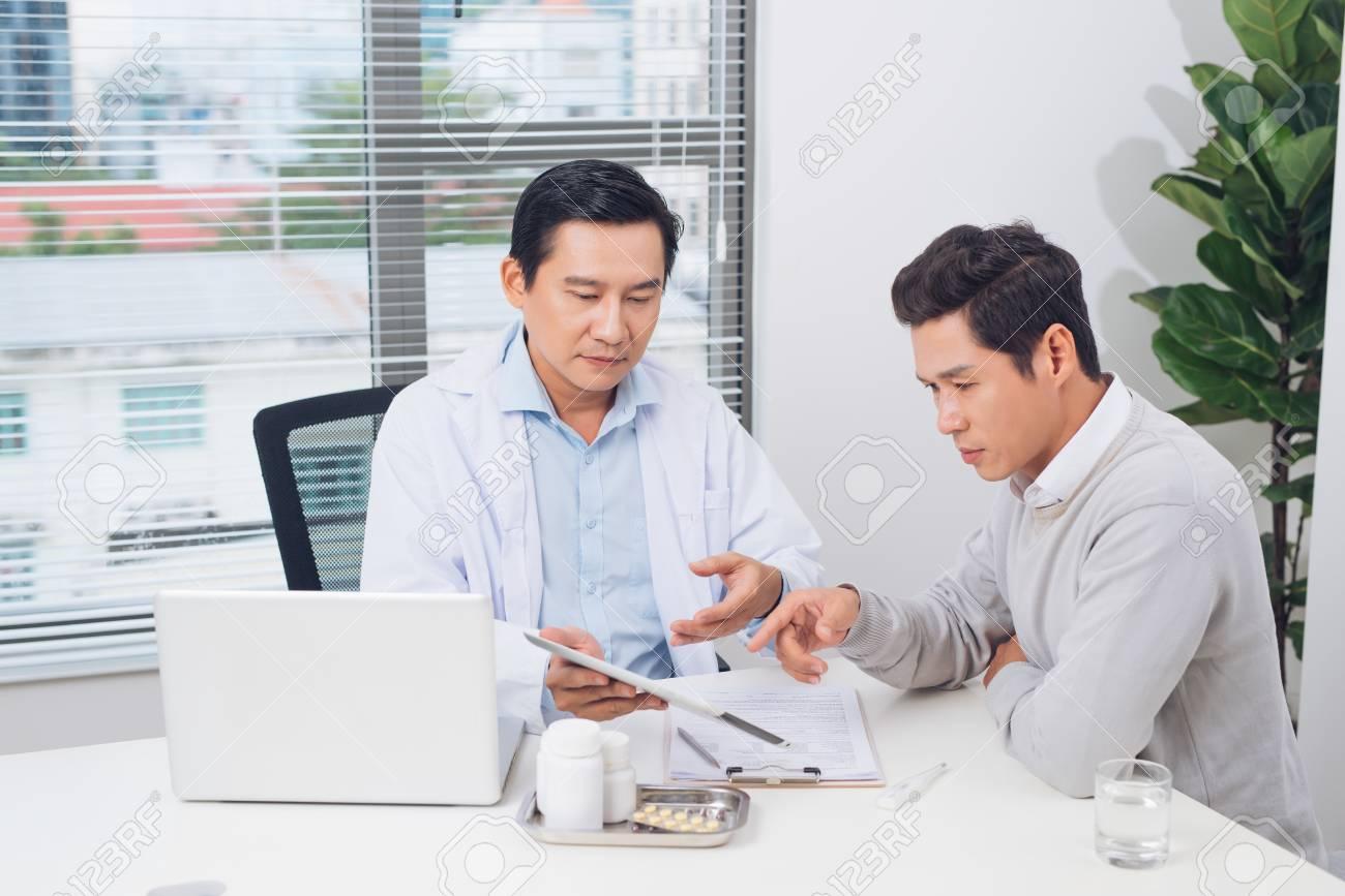 Doctor explaining prescription to male patient, healthcare concept - 97608470