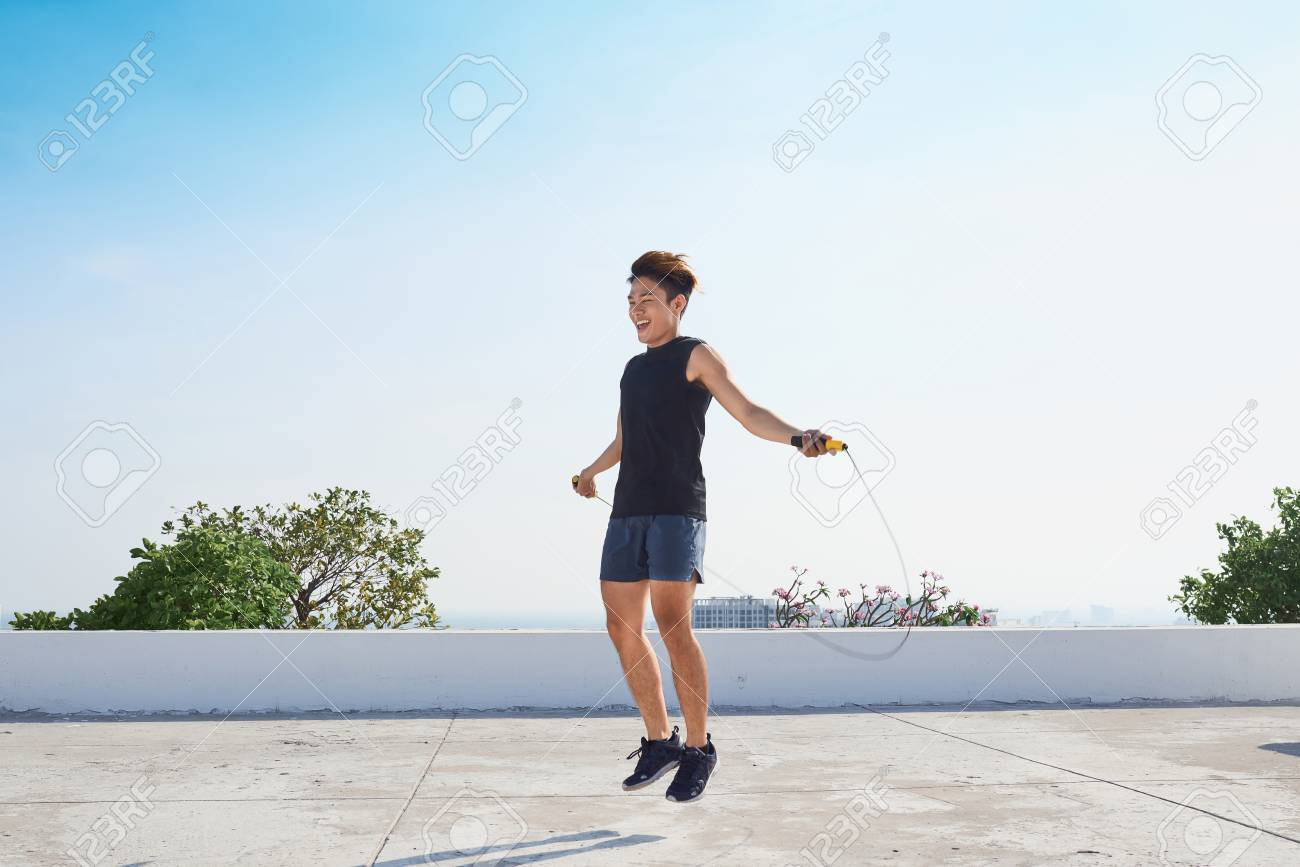Man jumping on the jumping rope. Young asian descent men with torso jumping on the jumping rope outdoors - 103825051