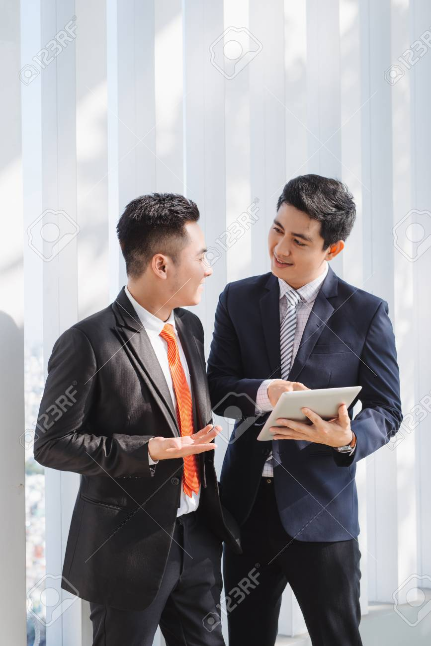 Two Vietnamese male coworkers talking and smiling - 105403555
