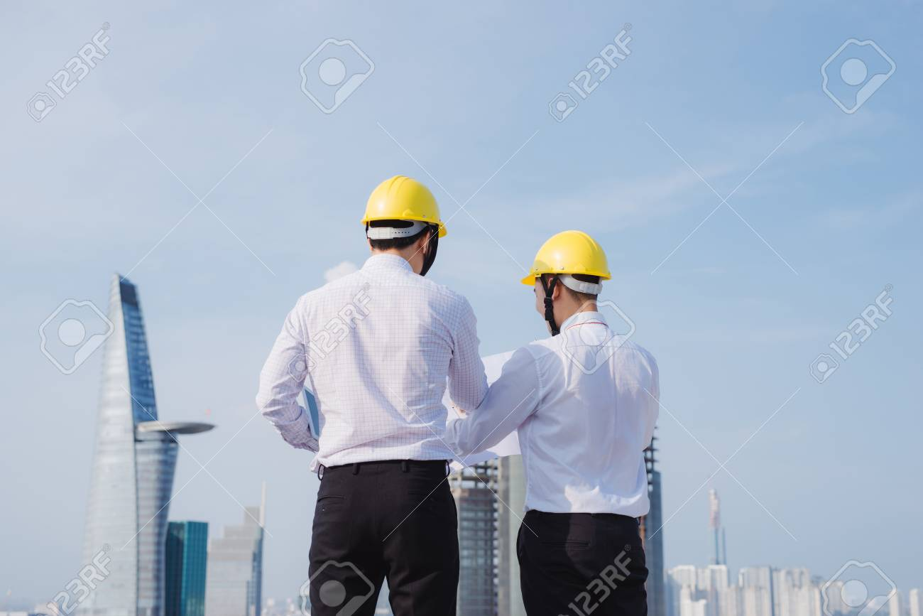 View of Two workers working outside with a tablet on a construction site - 104973252