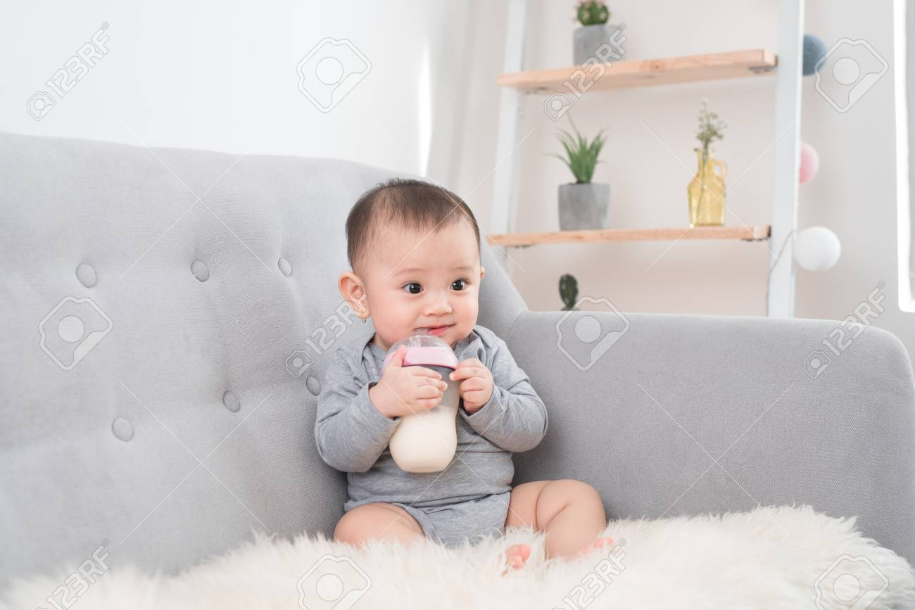 Little cute baby girl sitting in room on sofa drinking milk from bottle and smiling. Happy infant. Family people indoor Interior concepts. Childhood best time! - 109260682