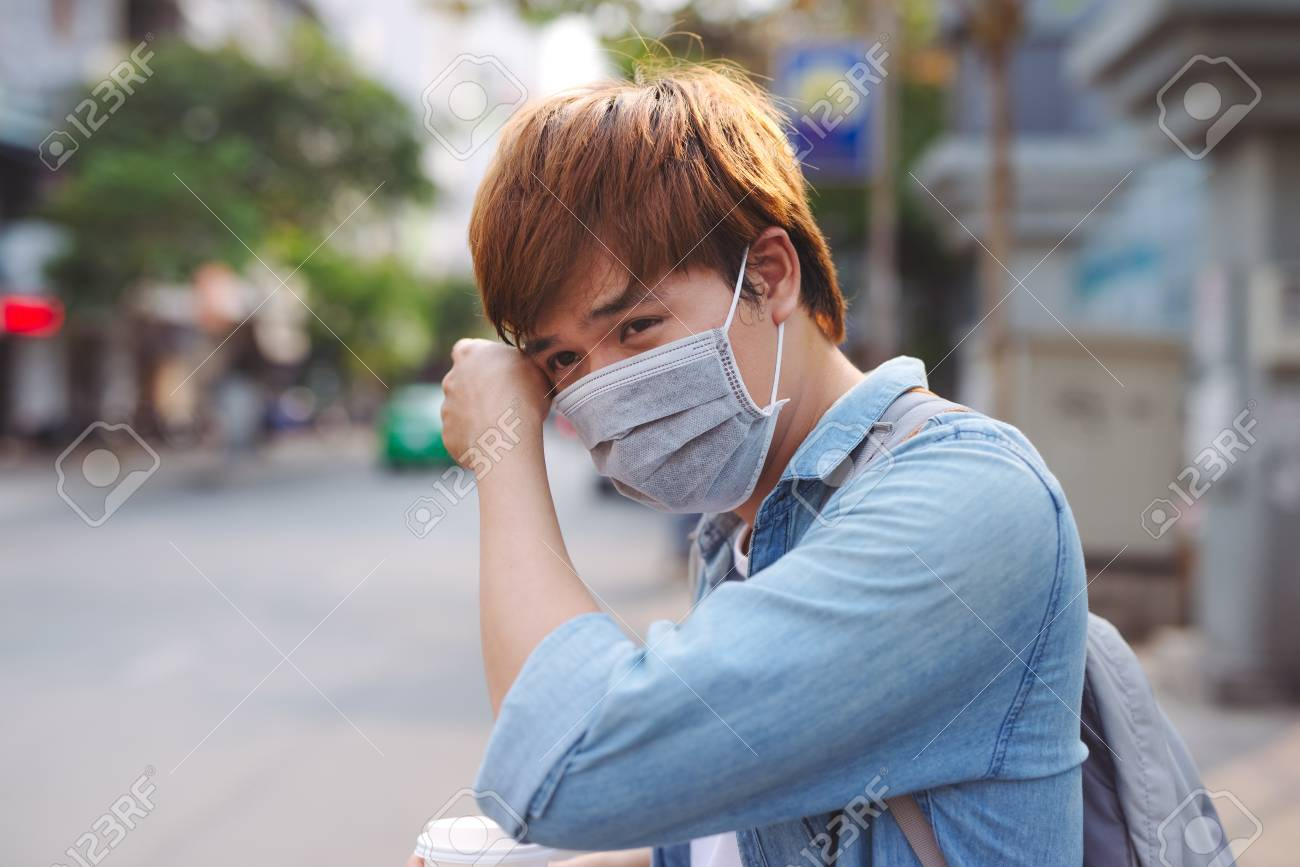 Asian man in the street wearing protective masks., Sick man with flu wearing mask and blowing nose into napkin as epidemic flu concept on the street. - 117404675