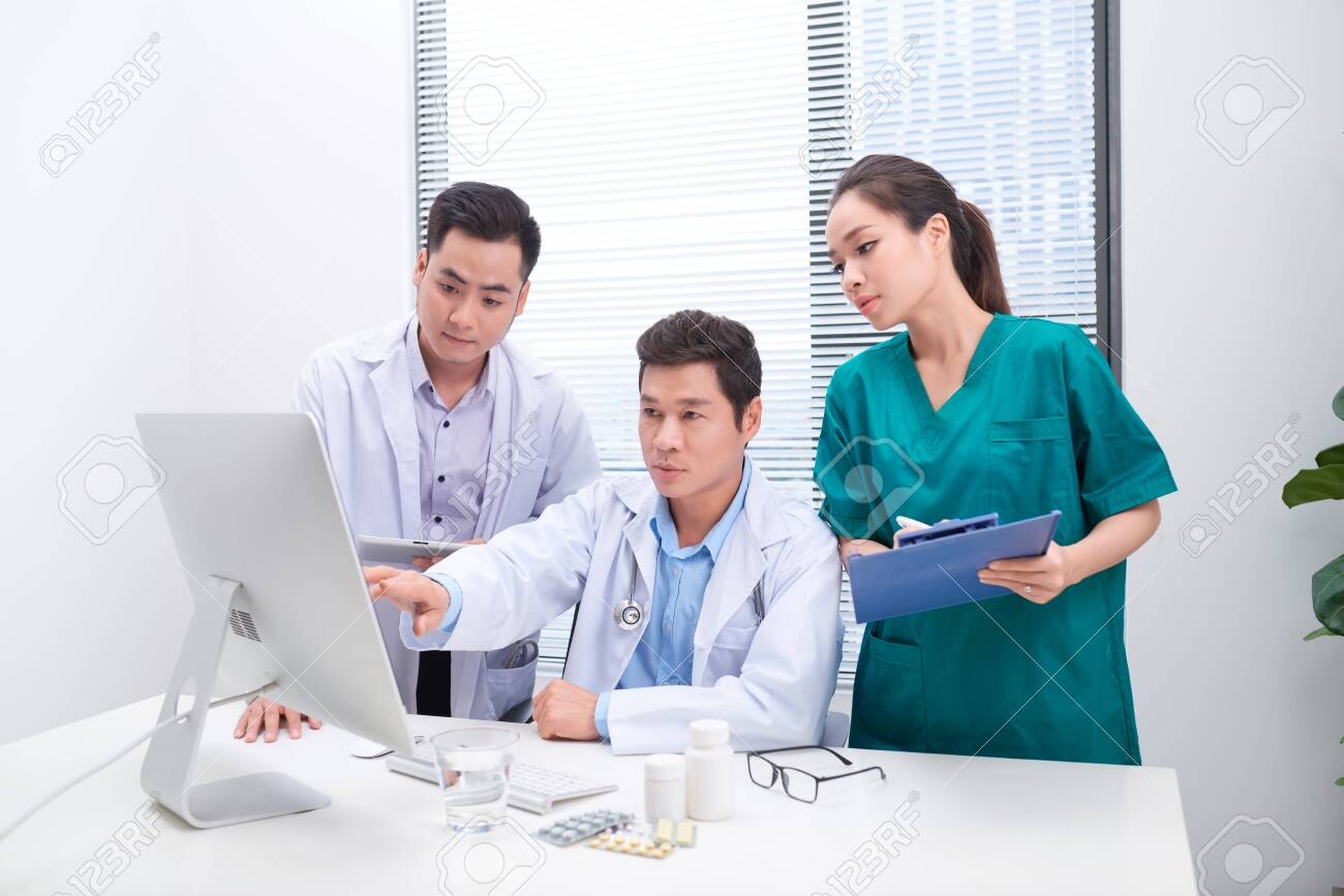 Three doctors discussing patient files on office. - 122835432