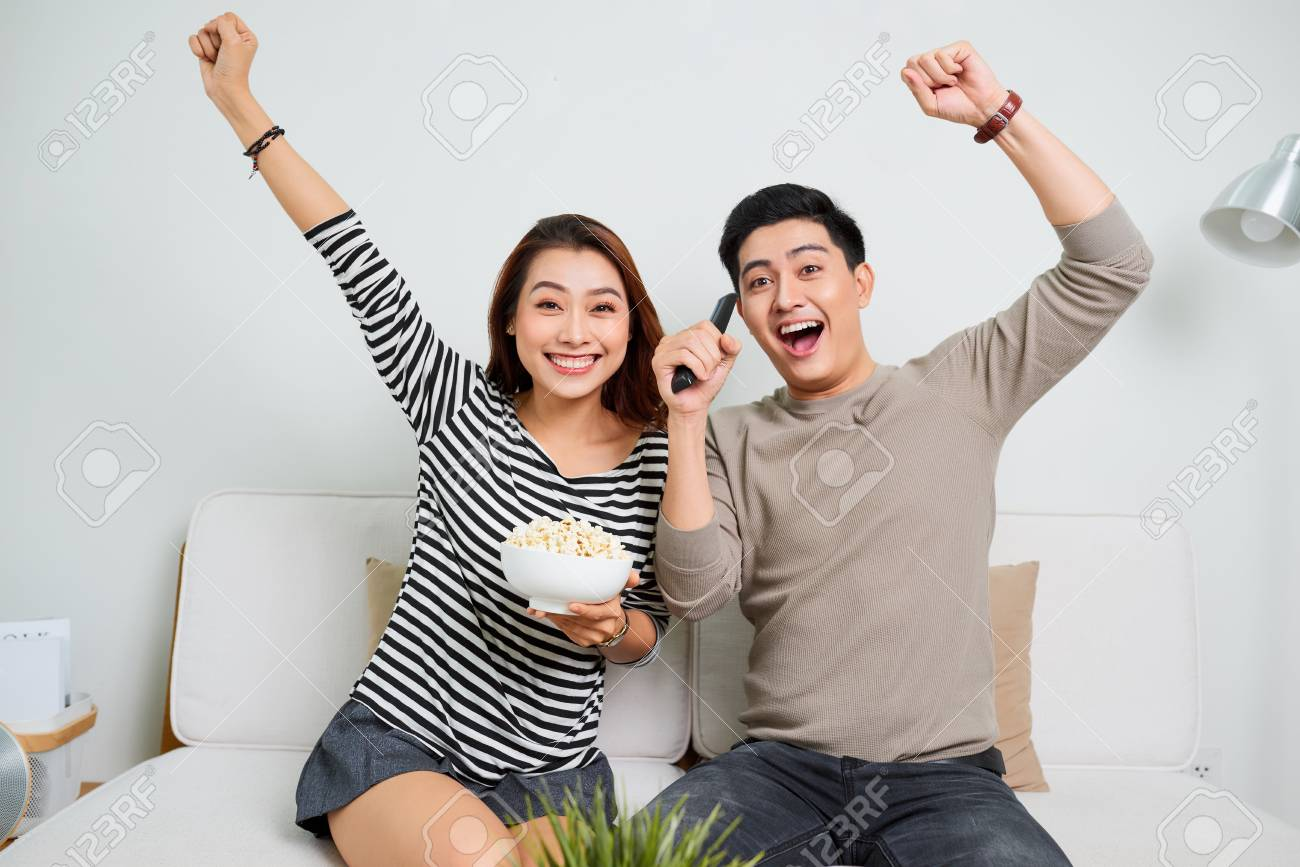 young handsome couple enjoying free time watching television with popcorn - 118567503
