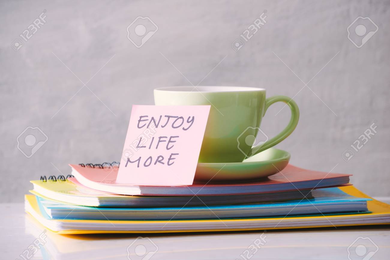 Green cup with sticker and notebooks on tabletop. - 119039224