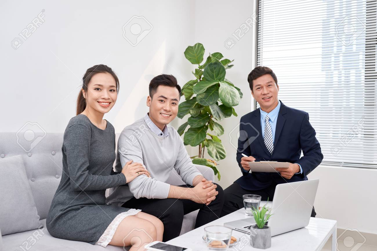 Successful lawyer giving consultation to family couple about buying house - 121036915