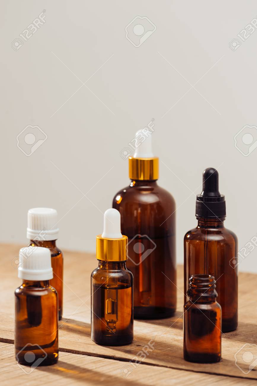 Essential oils bottles on wooden desk with candlelight beside. Spa wellness set. - 120516832