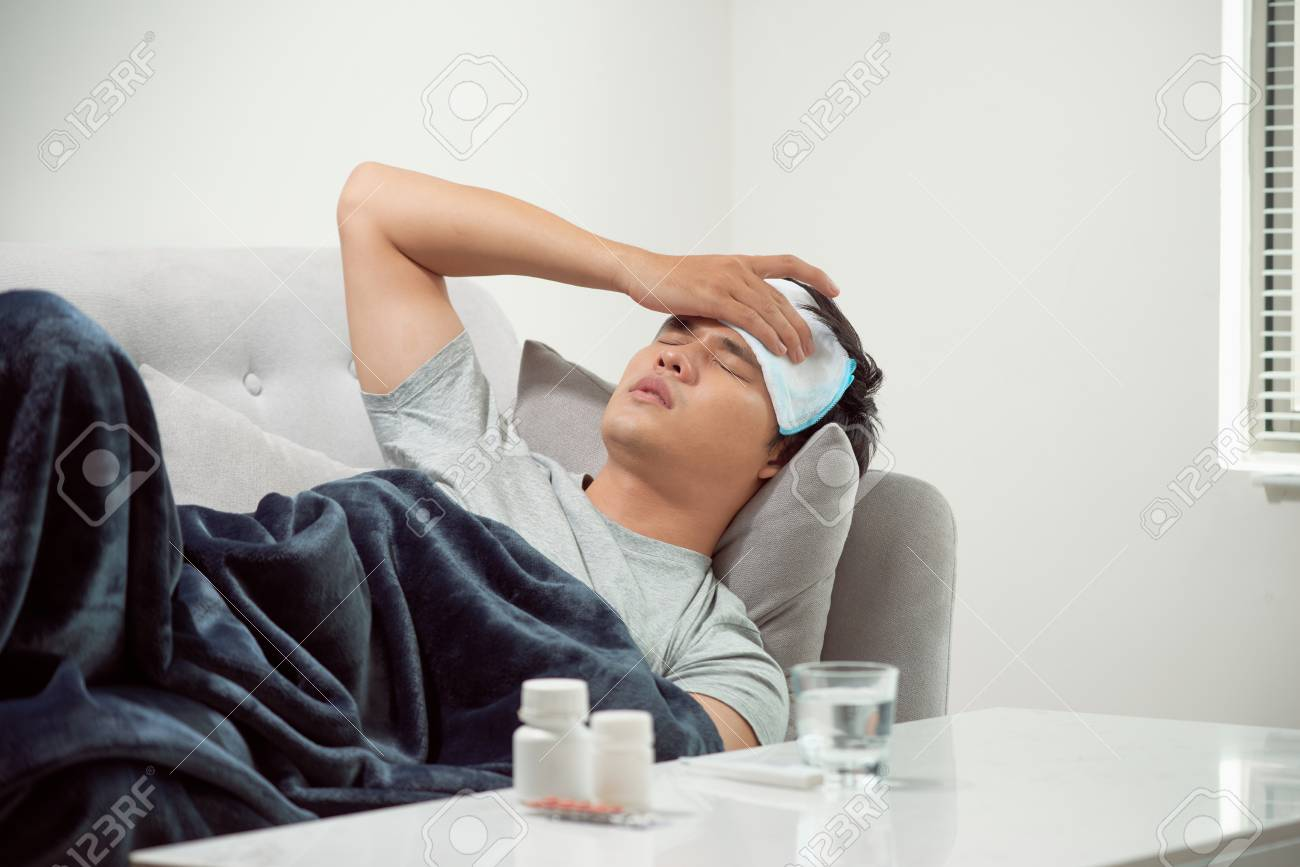 sick wasted man lying in sofa suffering cold and winter flu virus having medicine tablets in health care concept looking temperature on thermometer - 120518495