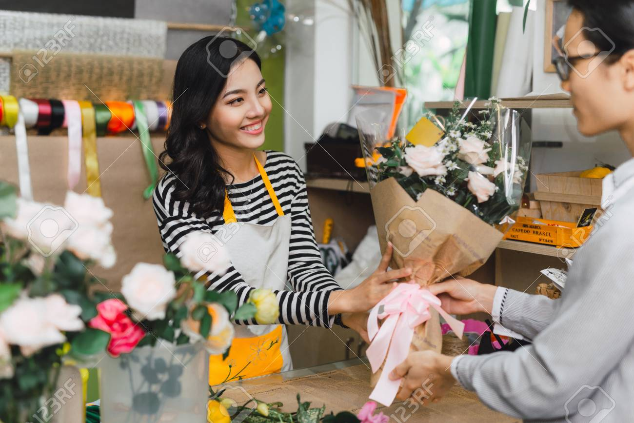 Ho Chi Minh City, Vietnam - 21 August, 2017: happy smiling florist woman making bouquet for and man or customer at flower shop - 122855219