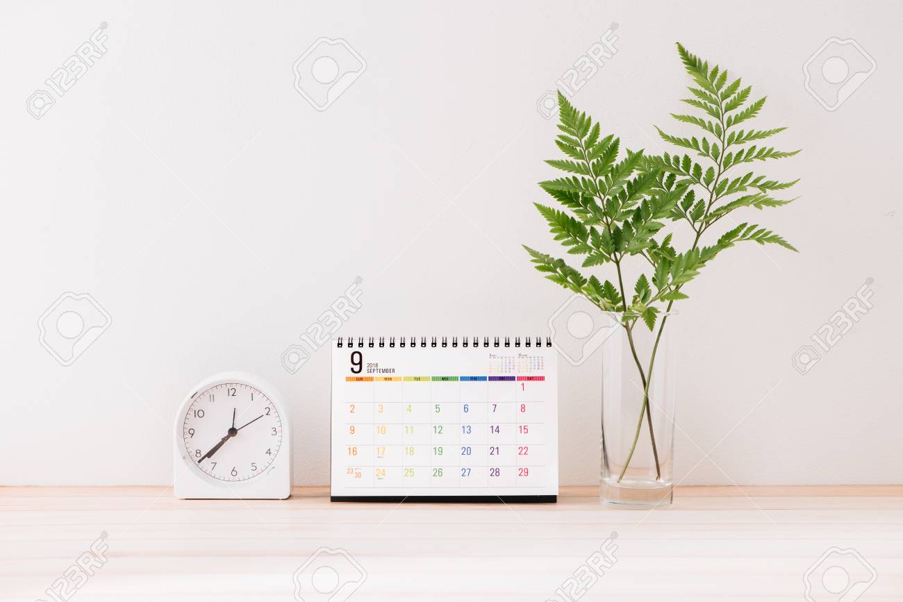 Mockup with a calendar with a white center against the background of a white wall with a alarm clock, leaves in vase - 121062989