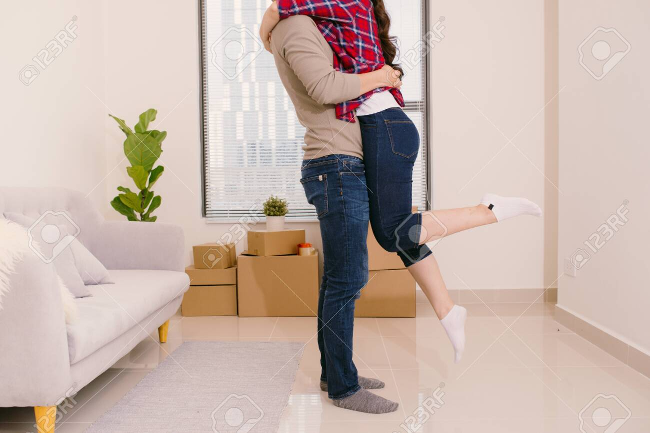 Just married couple of young man and woman feeling unbelievable chilling in their new house - 121037452