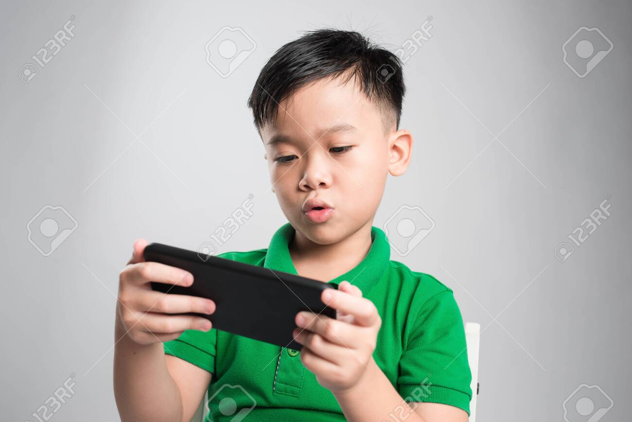 Portrait of an amused cute little kid playing games on smartphone isolated over gray background - 121037571