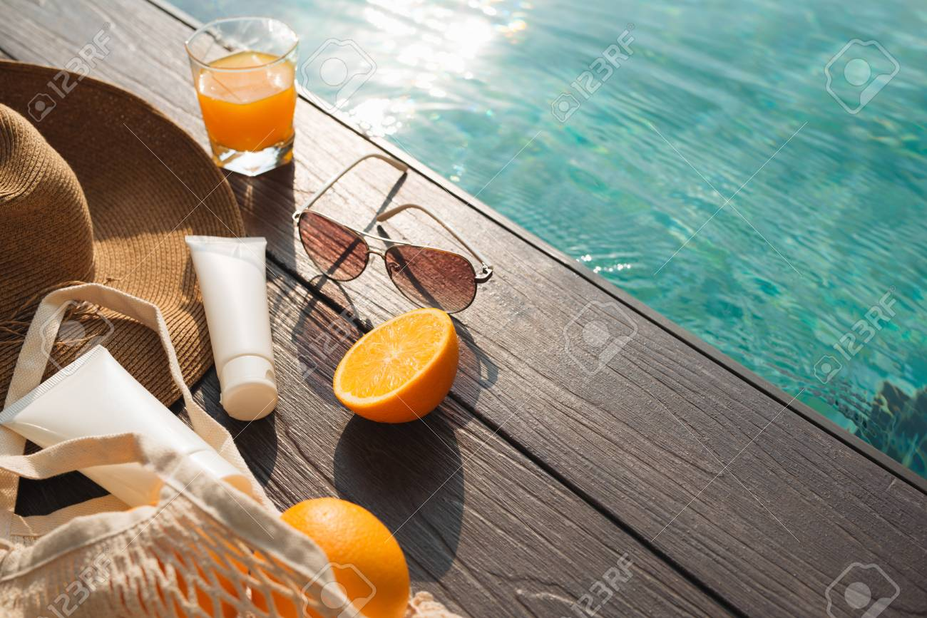 Beach hat, orange juice and sunglasses near the swimming pool - 121137672