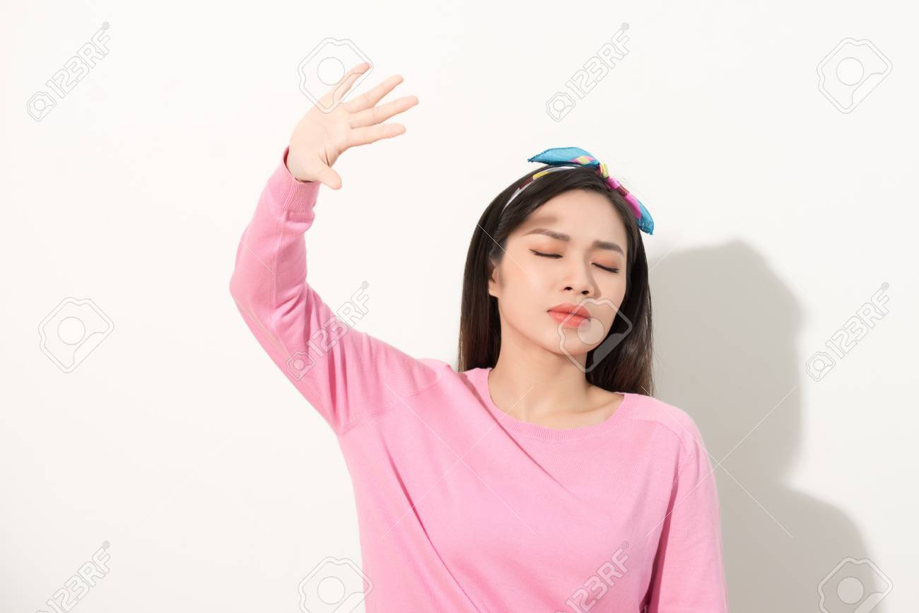 Portrait of a beautiful Asian girl covering face by hand of bright sun light. woman in a pink dress protecting her face from solar light. Skin care or beauty concept - 121249199