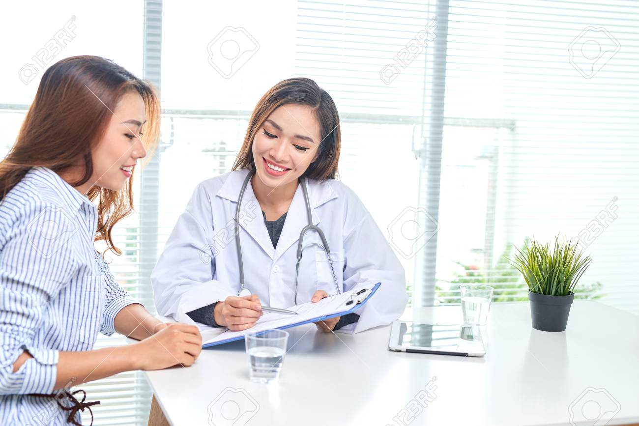 Female doctor talks to female patient in hospital office while writing on the patients health record on the table. Healthcare and medical service. - 121990403