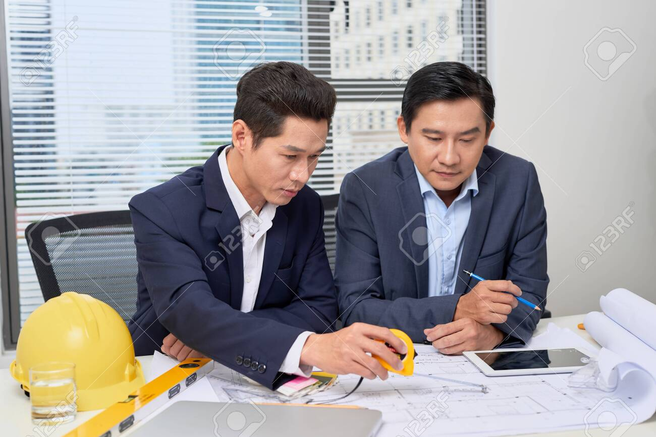 Coworkers working in office. Business people planning over desk - 121991115
