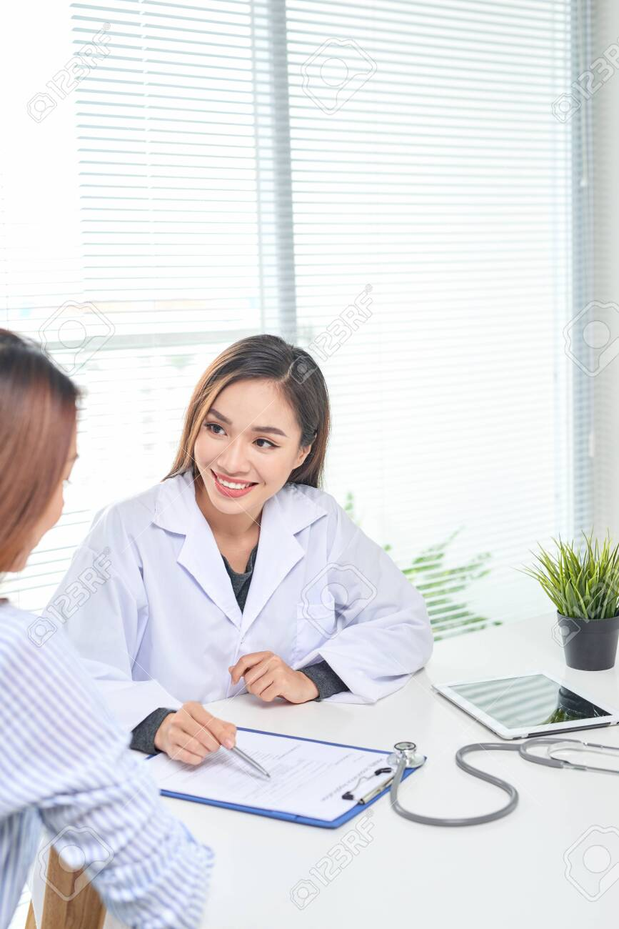 Female doctor talks to female patient in hospital office while writing on the patients health record on the table. Healthcare and medical service. - 121991344