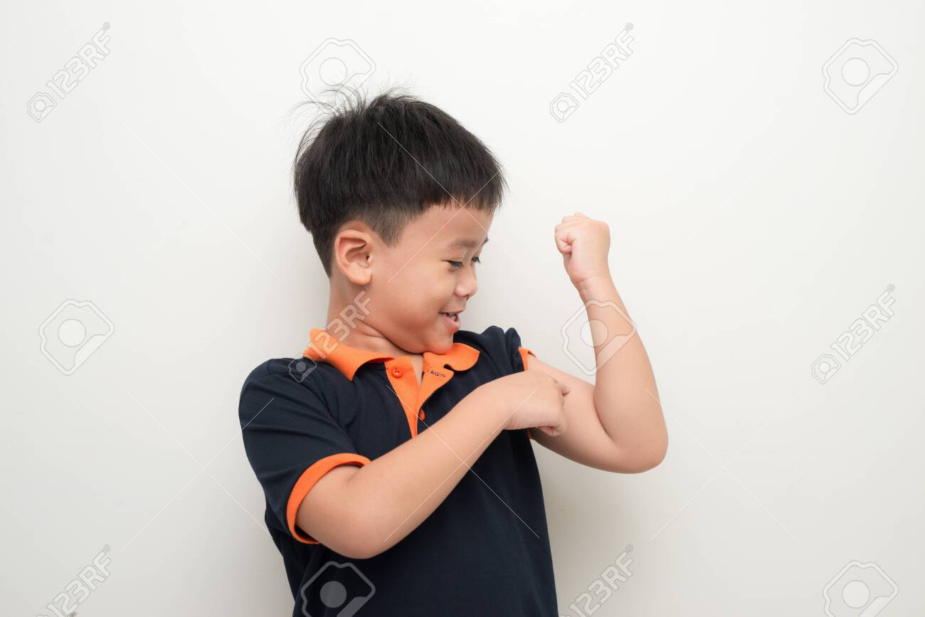 Young asian boy pointing his bicep to tell he is strong - 124787469