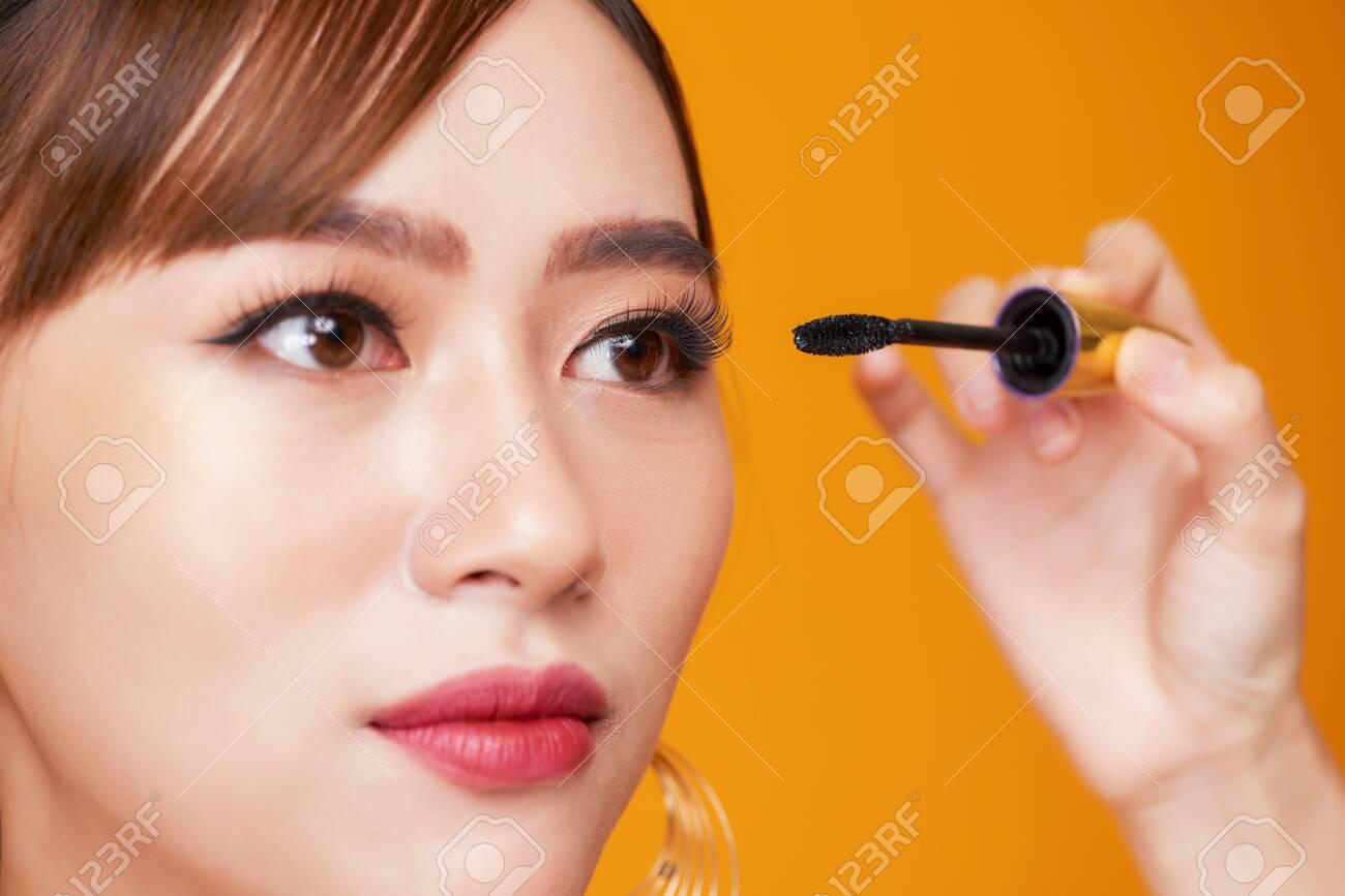 Beautiful woman applying mascara on her eyelashes - 125688605
